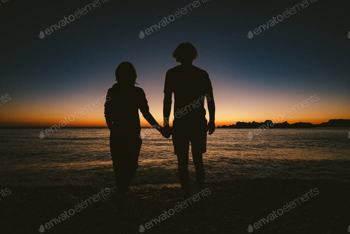 Silhouette eines liebenden Paares auf orangefarbenem Sonnenuntergang