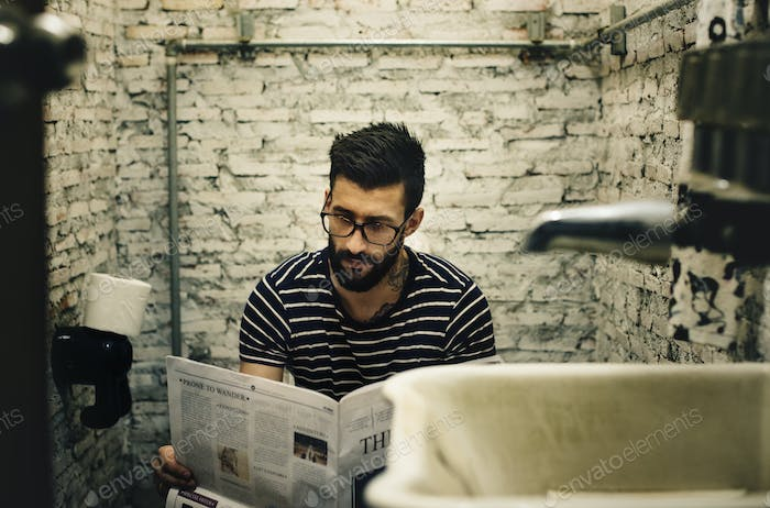 Man in a restroom reading newspaper