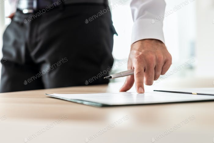Businessman standing next to his desk pointing to a document where to sign it