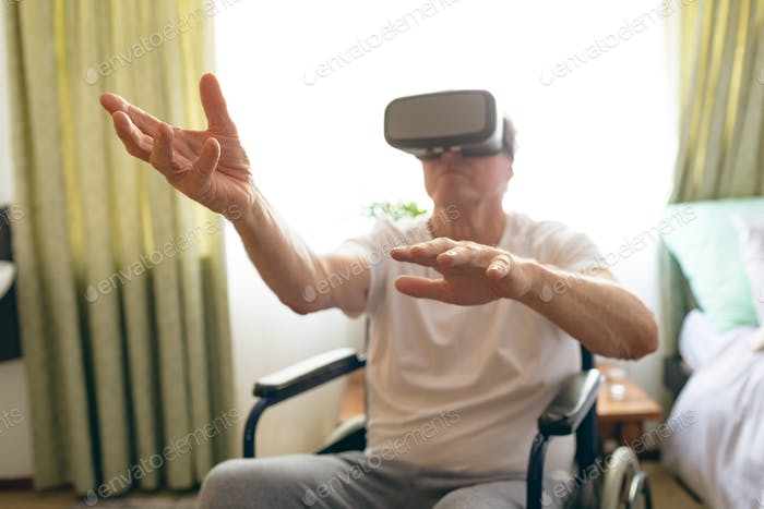 Male patient using virtual reality headset in wheelchair at retirement home