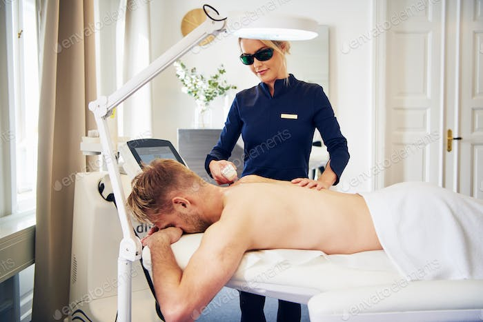 Young beautician performing laser hair removal on a male client