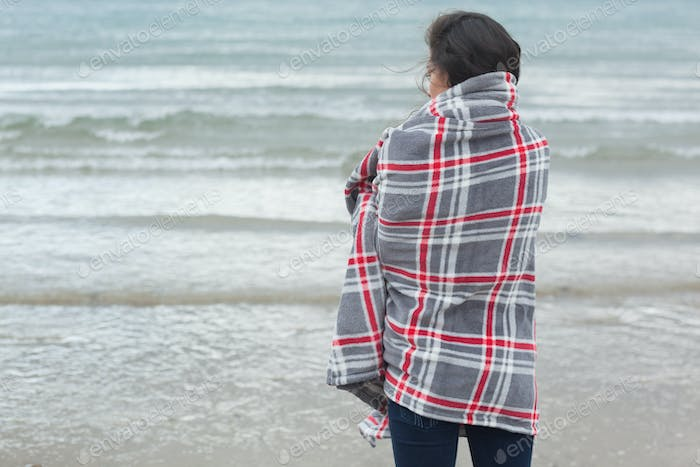 Rear view of a young woman covered with blanket looking at the sea on beach