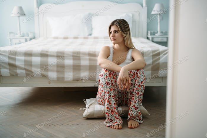 Depressed young woman sitting on bed at home