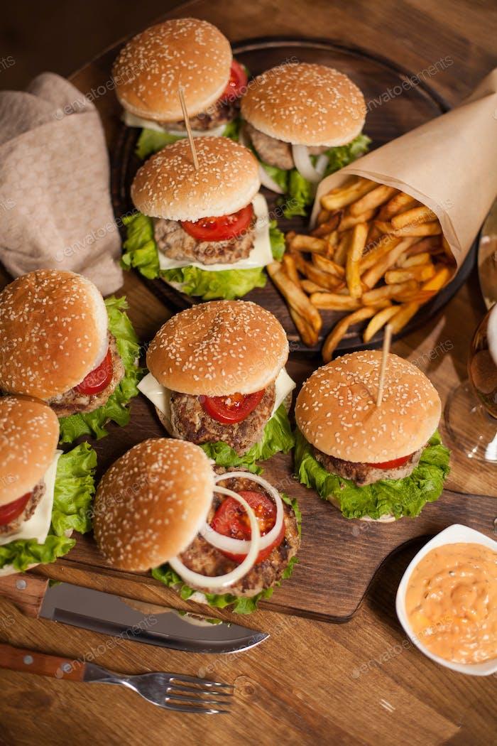 Draufsicht der leckeren Burger auf Holztablette neben dem Kochmesser