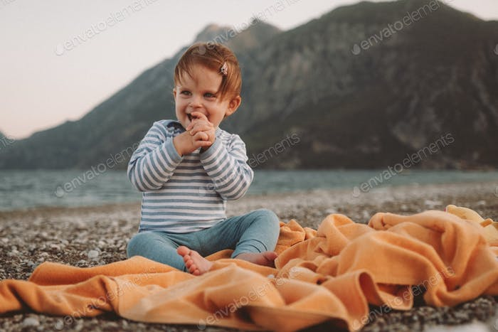 Cute little baby girl playing on a beach in summer day. Family Travel and vacation concept