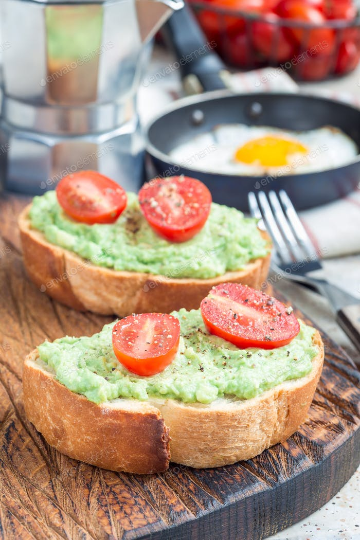 Open sandwich with mashed avocado and cherry tomatoes, sprinkled with black pepper, vertical