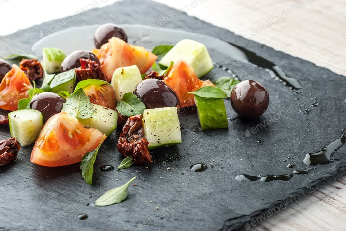 Salad with fresh and dried tomato and olives on the black stone close-up