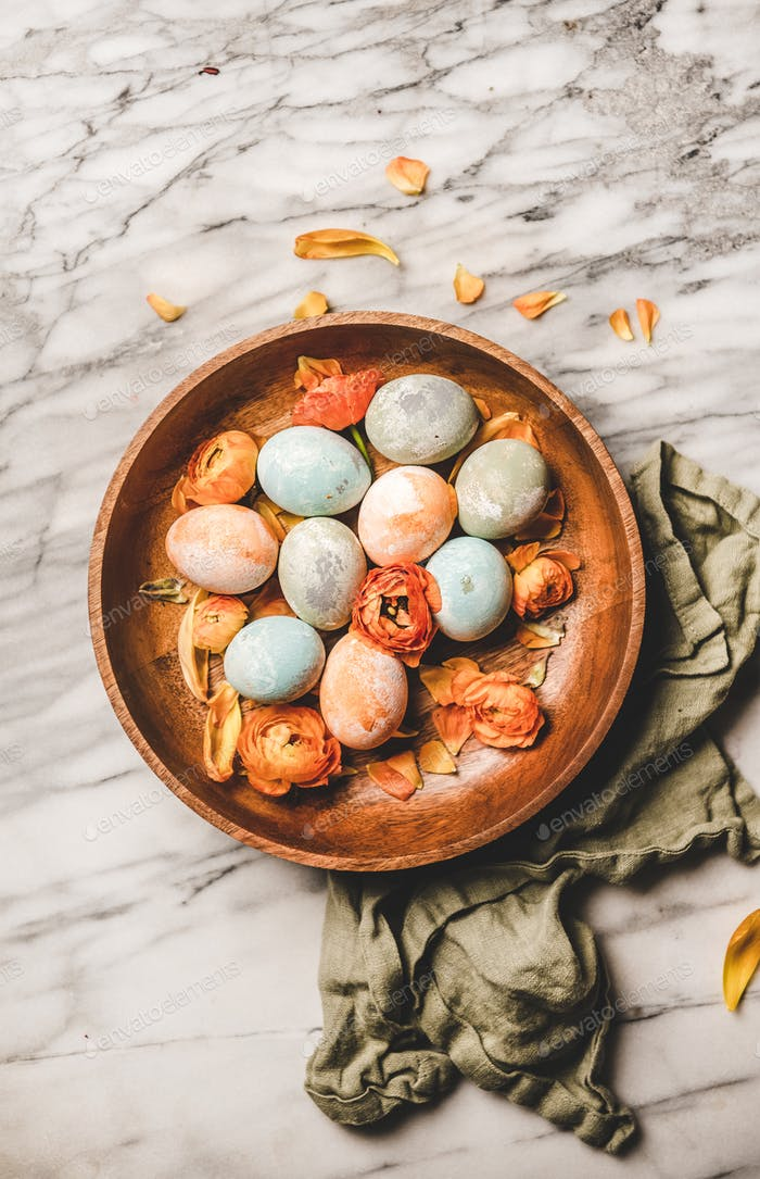 Dyed Easter eggs and blossom flower petals in wooden plate
