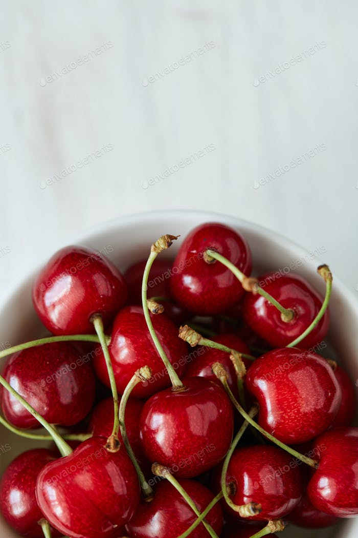 Some sweet cherries with green stems and leaves in the white cer