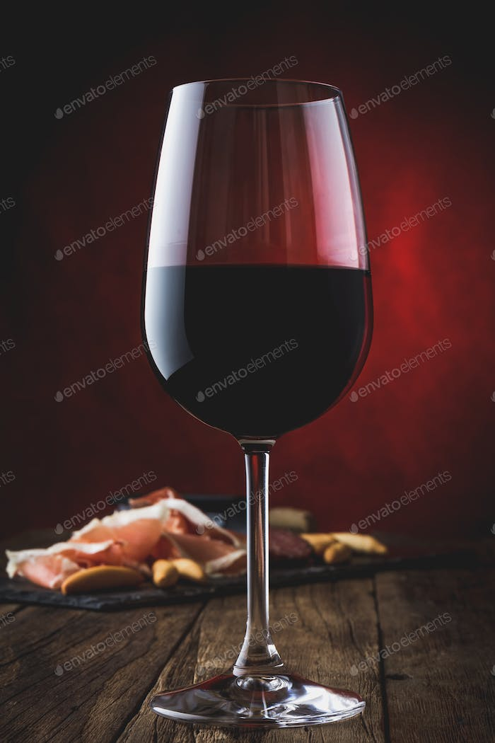 Glass of red wine with ham serrano on wooden background.