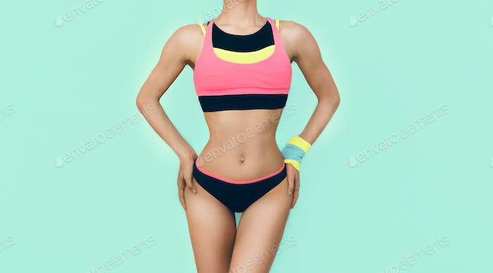 slim athletic girl in bright trendy sport clothes on blue backgr