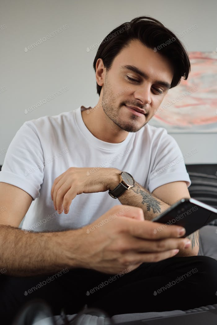 Young smiling brunette man in white T-shirt dreamily using cellphone sitting on bed with laptop