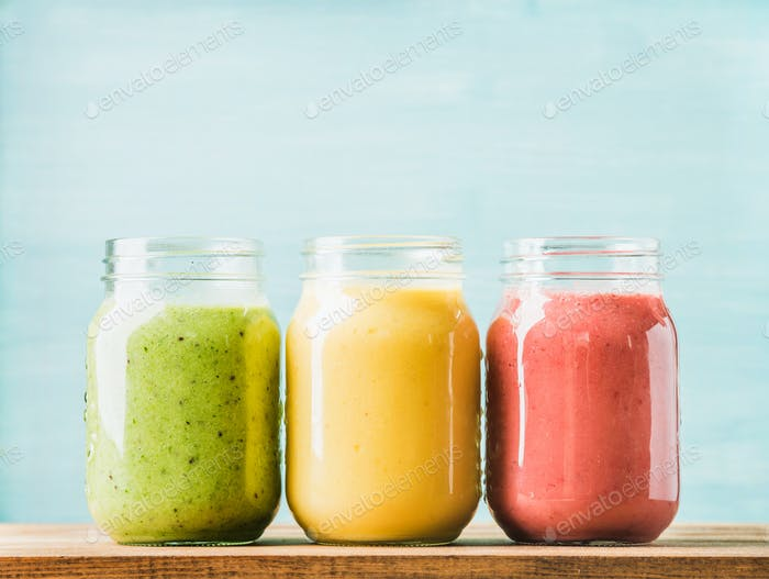 Fresh blended fruit smoothies of various colors and tastes in glass jars. Green, yellow, red.