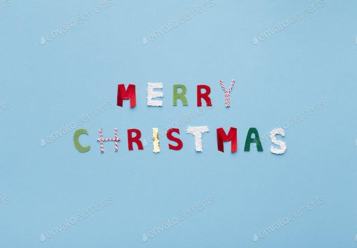 Frohe Weihnachten Text von farbigen Buchstaben auf blauem Hintergrund