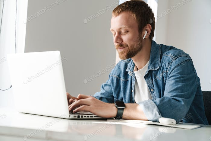 Photo of pleased man using wireless earphones while working with laptop