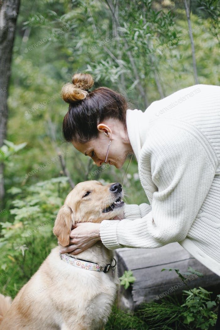 A woman petting her dog.