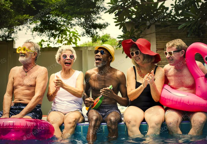 Group of diverse senior adults sitting by the pool enjoying summ