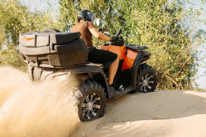 Atv riding in action, sand quarry on background
