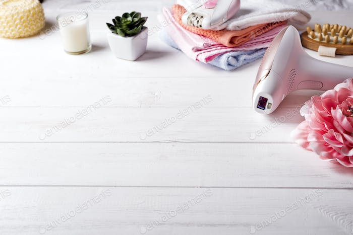 Modern laser epilator with bath accessories on white background.