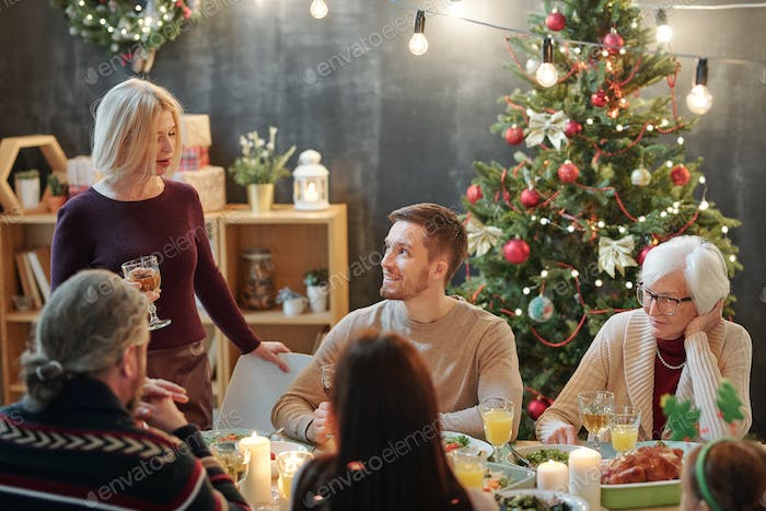 Members of big family looking at mature blonde woman with glass of wine