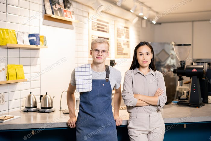 Two young workers of contemporary cafe or restaurant standing by workplace