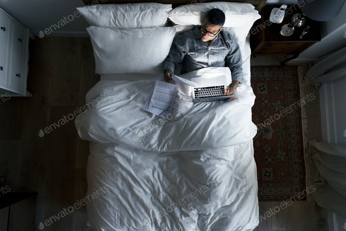 Business man on bed working at night