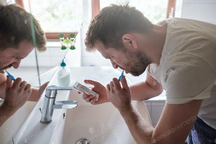 Junge kaukasische Mann im Bad putzt seine Zähne während SMS auf Handy