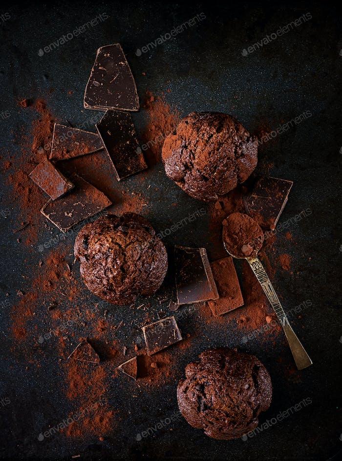 Schokoladenmuffin auf dunklem Hintergrund. Draufsicht. Flache Lag