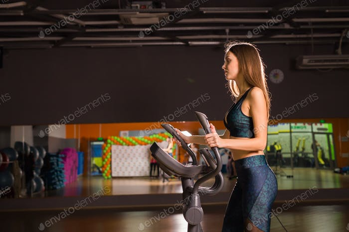 Beautiful gym woman exercising on a cardio machine