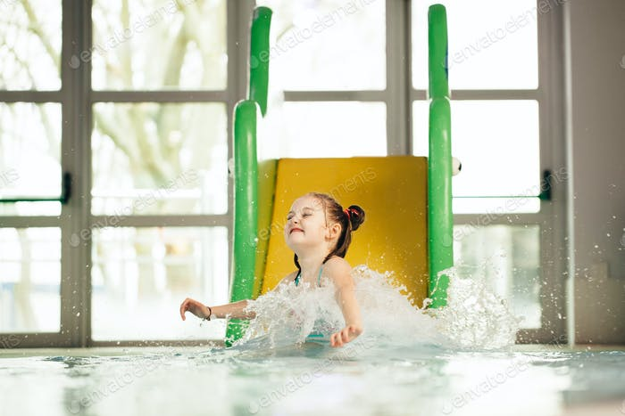 Little girl sliding down the water slide