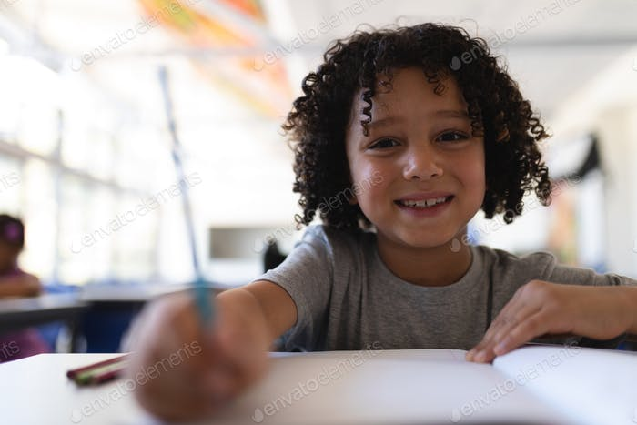 Front view of happy schoolboy looking at camera at desk in classroom of elementary school