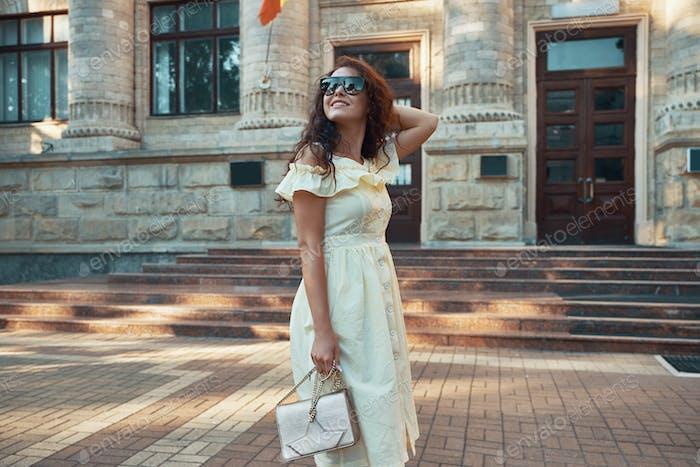 Fröhliches Mädchen, das durch die Stadt läuft.