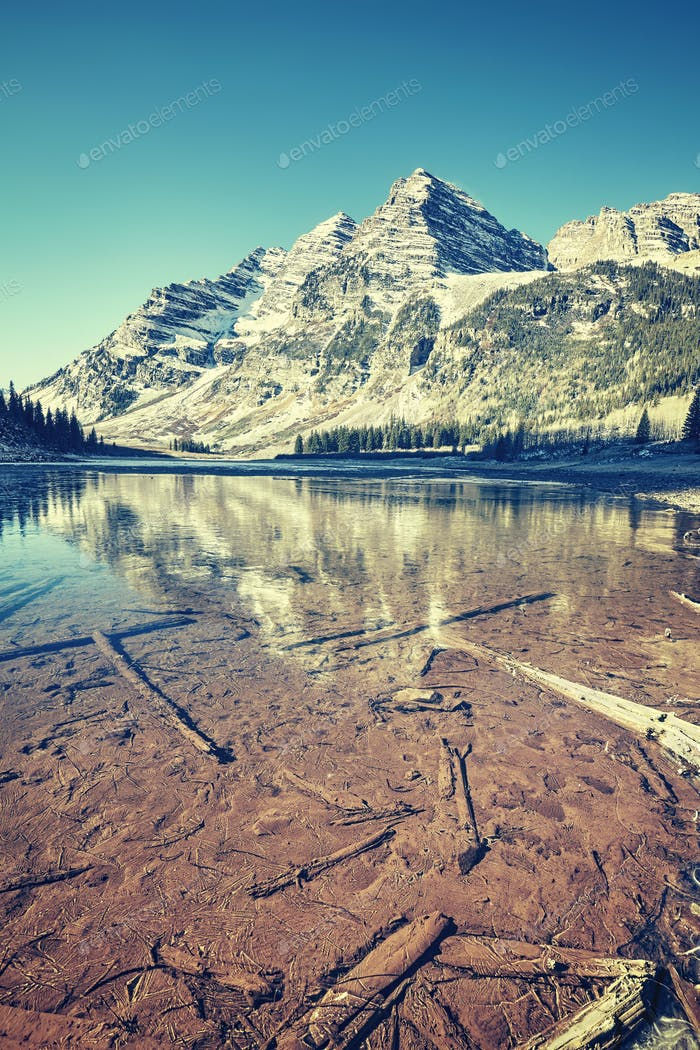 Vintage toned Maroon Bells reflected in frozen lake, Colorado, U