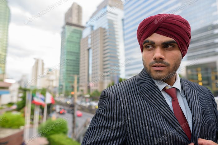 Portrait of Indian businessman with turban thinking in city