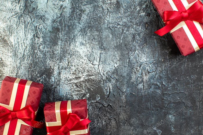 Gifts in beautifully packaged boxes and tied with satin ribbon on dark background