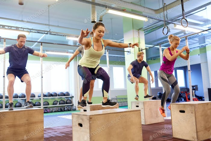 group of people doing box jumps exercise in gym