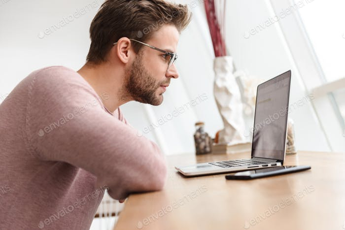 Image of young bearded man working on laptop computer by window in cafe