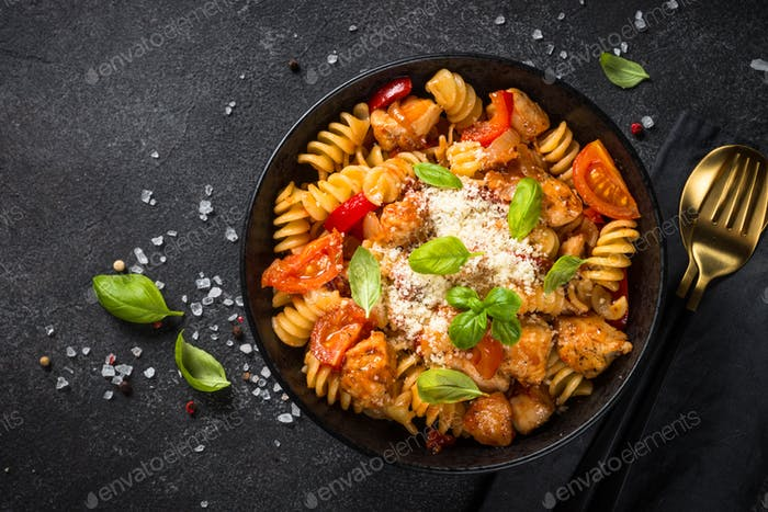 Pasta chicken with vegetables on black.