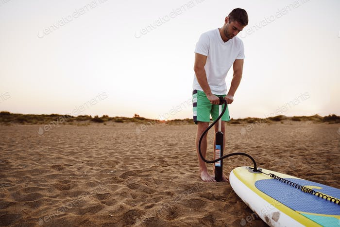 Young man inflating paddle sup board on the beach at sunrise
