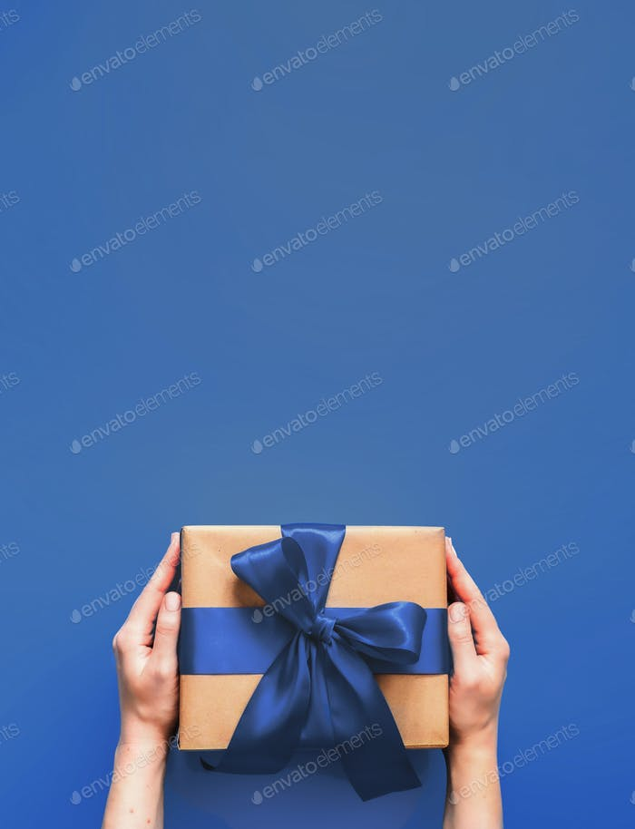 Female hands hold gift box on blue 2020 color