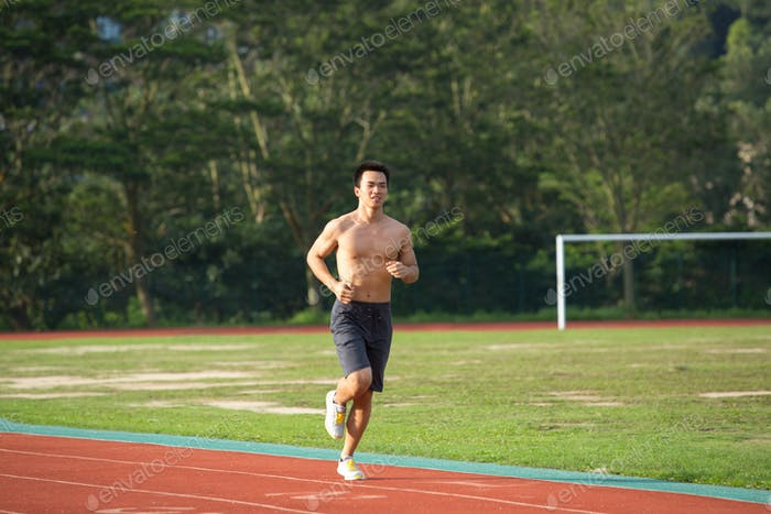 Young Asian man doing exercise outdoors