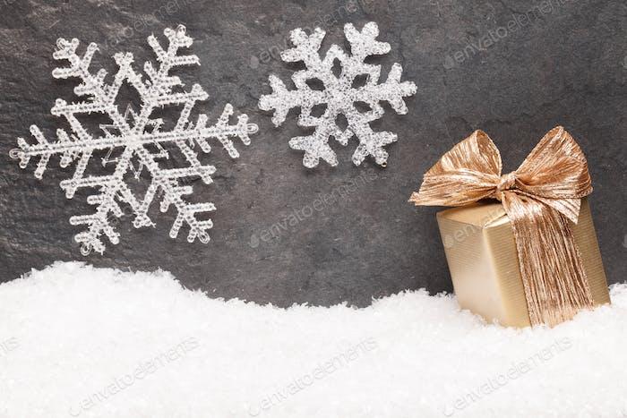 Weihnachts-Grußkarte Noel festlicher Hintergrund. Neujahrssymbol. Goldene Geschenkbox auf Schnee.
