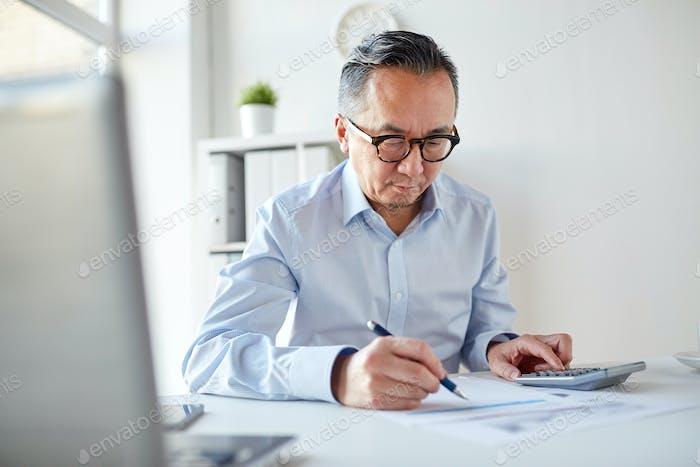 Geschäftsmann mit Taschenrechner und Papiere im Büro
