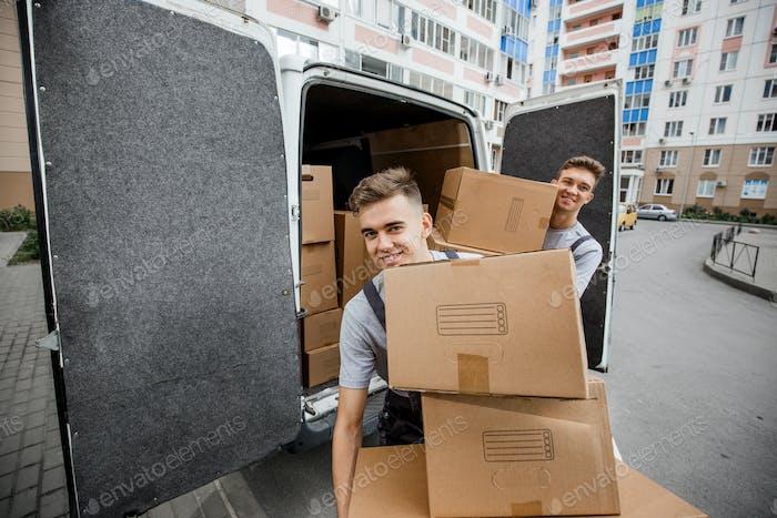 Zwei junge, hübsche lächelnde Arbeiter, die Uniformen tragen, entladen den Wagen voller Kisten. Der Block