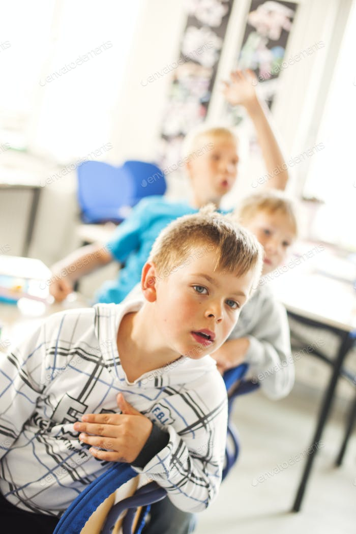 Cute boy looking away while sitting in classroom