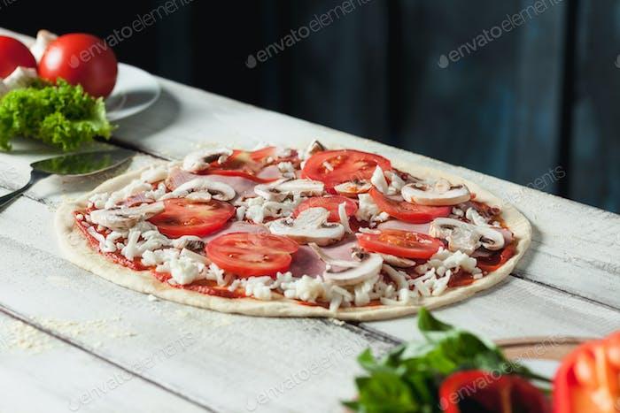 Nahaufnahme einer hausgemachten rohen Pizza mit Käse und Tomatensauce auf einem hölzernen Hintergrund