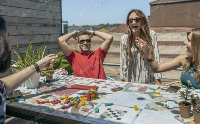 Office workers playing with tower wooden stacking on terrace