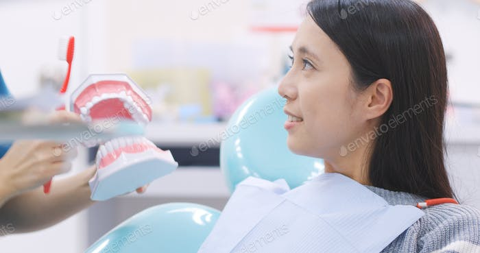 Dentist showing patient how to brush teeth in dental clinic