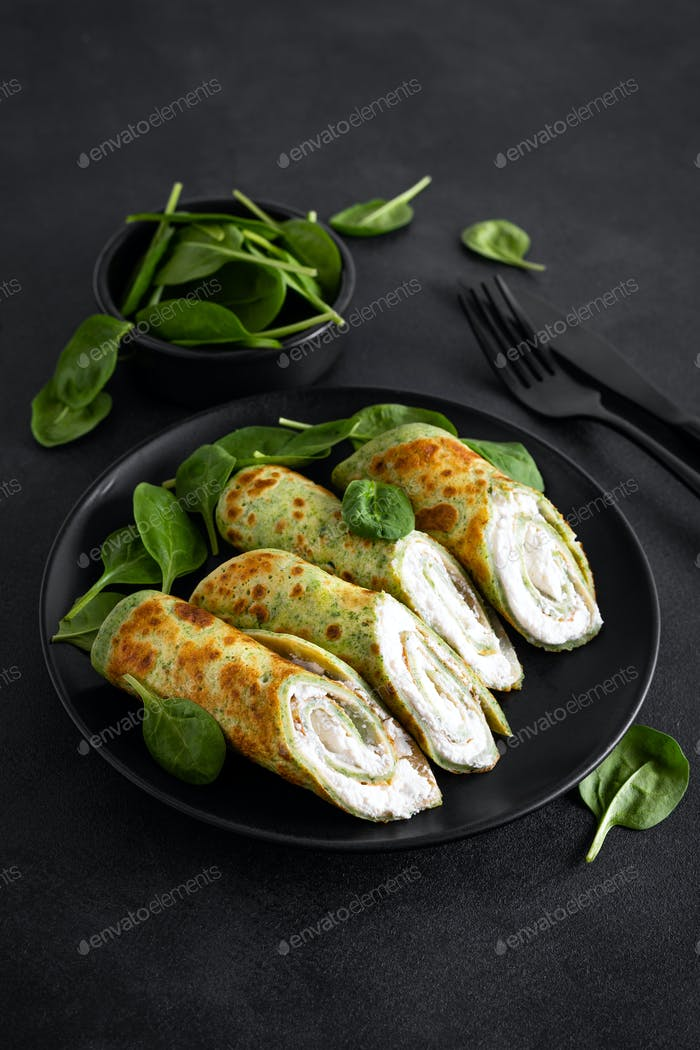 Savory crepes with spinach and feta cheese on black background