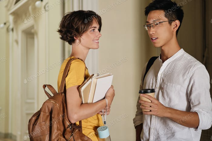 Two young attractive international casual students happily talking in corridor of university